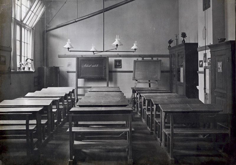 Empty classroom of the Sophie Rosenthal Primary School, The Netherlands, 1913. On the blackboard is written:  Arbeid adelt [There is nobility in labour]. Photo: Nationaal Archief/Collectie Spaarnestad/Het Leven/Fotograaf orbekend
