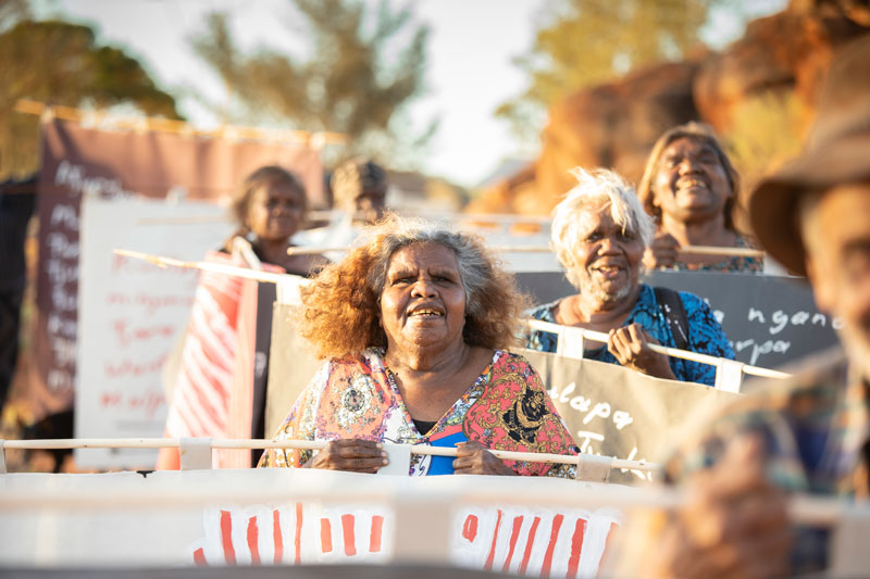 Tuppy Goodwin (centre) and other Mimili community members march with their banners for the Biennale of Sydney. Photo: Meg Hansen. Courtesy Mimili Maku Arts