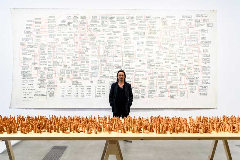 Sawangwangse Yawnghwe with his exhibited works at the 9th Asia Pacific Triennial of Contemporary Art (APT9), QAGOMA Brisbane. Image courtesy the artist and Queensland Art Gallery | Gallery of Modern Art. Photo: Chloe Callistemon