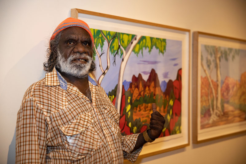 Mervyn Rubuntja in front of Mt Zeil, Central Australia. Photo by Oliver Eclipse. Courtesy Araluen Arts Centre, Alice Springs