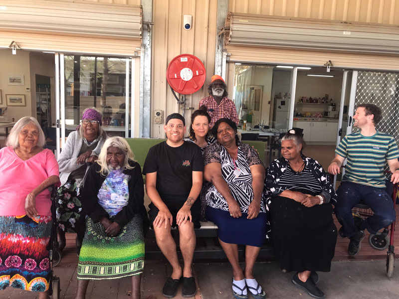 Iltja Ntjarra artists at their studio with Tony Albert. Front row, from left: Noreen Hudson, Ivy Pareroultja, Tony Albert, Vanessa Inkamala, Kathleen France and Harry Copas (Albert's assistant). Middle row: Gloria Pannka and Koren Wheatley (coordinator). Rear: Mervyn Rubuntja