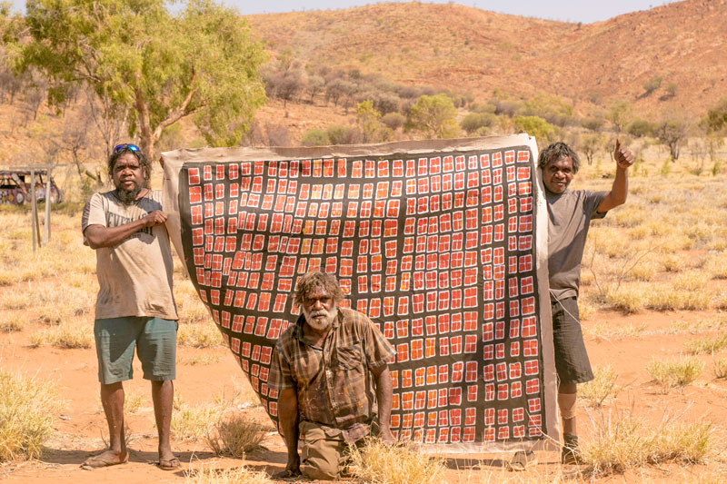 At the men's painting camp in October 2018, Carbiene McDonald with his first work, together with Aaron Kingsley and Snowy McDonald. Courtesy Papunya Tjupi Arts, Papunya