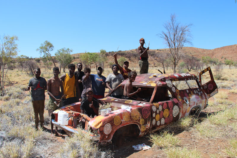 Young men learning to paint rockhole motifs at the men's painting camp in October 2018. Courtesy Papunya Tjupi Arts, Papunya
