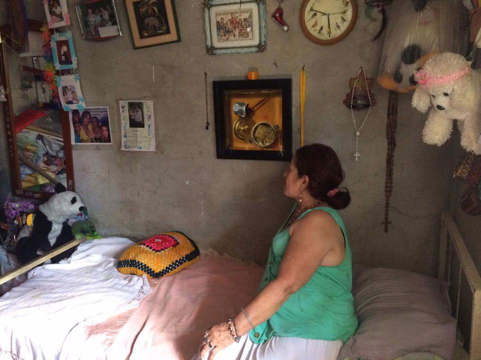 A woman regards the photograph of the reliquary that she received during the events at the Museo de Antioquia, which is now installed in her home in the hills of Antioquia. Photograph sent to the artist by one of the bereaved families