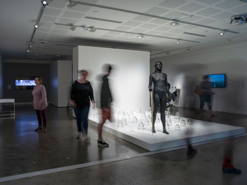 Nell, A white bird flies in the mist, a black bird flies in the night, a woman walks, wild and free, she is not afraid to die, bronze, mother of pearl, resin, 33 individually hand-blown clear glass ghost sculptures, 2008. Instillation view, Lismore Regional Gallery. Photo: Carl Warner