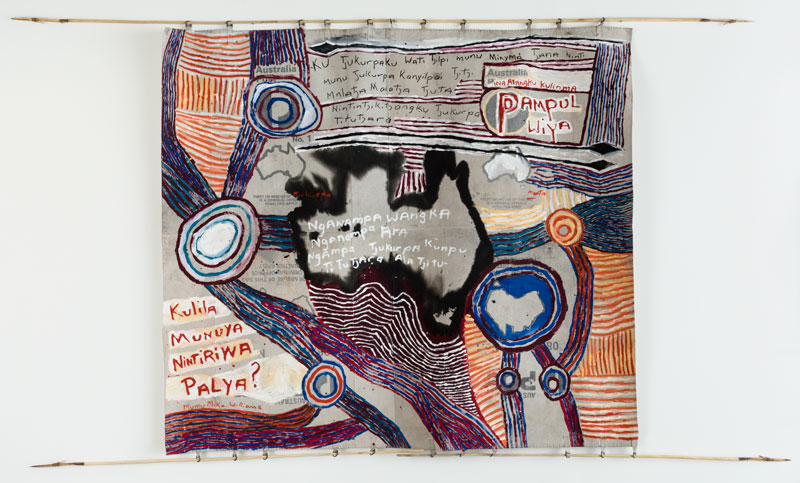 Mumu Mike Williams with Sammy Dodd (spears), Postbag Painting, 2017, synthetic polymer paint on canvas mailbag; wood, kangaroo tendon. Artbank collection, purchased 2017.  Text in English: Australia's Tjukurpa is held and managed by our senior men and women.  They are the ones who are keeping our Tjukurpa strong for new generations  of children coming up, and will continue to teach it, always.  Australia, open your ears and remember this.  Do not damage our cultural heritage.  Theft or misuse of this Tjukurpa is a criminal offence. Penalties apply.  Theft or misuse of this land is a criminal offence. Penalties apply.  Our language, our cultural identity and our Tjukurpa are strong and enduring.  Listen and learn, okay?