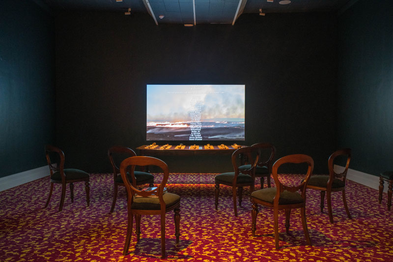 Julie Gough, The Gathering, 2015, 2019, HDMI video, sound, edited by Jemma Rea, colonial table, enamel on Tasmanian oak, 28 found stones, carpet; Julie Gough with Margaret Woodward, Entitled (red), 2019, designer Jet® bespoke carpet, custom made by Godfrey-Hirst Australia. Installation view, Julie Gough: Tense Past, Tasmanian Museum and Art Gallery. Photo: Alastair Bett