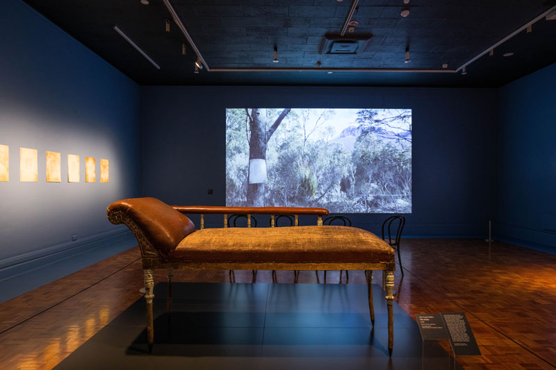 (Front) Julie Gough, The Chase, 2008, leather, tea tree, steel pins. Collection National Gallery of Australia, Canberra; (Back) Hunting Ground (haunted), 2016–17, video, sound; (Left) Hunting Ground (haunted), 2016, etching and acrylic silkscreen, printed at Cicada Press, University of New South Wales. Installation view, Julie Gough: Tense Past, Tasmanian Museum and Art Gallery. Photo: Alastair Bett